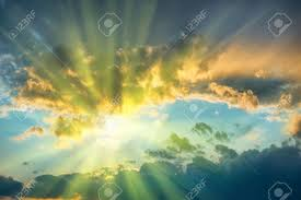 beautiful blue sky with sun shining through clouds stock photo