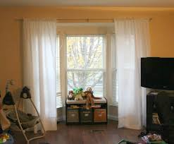 decorating bay window curtain rod with decorative cushions