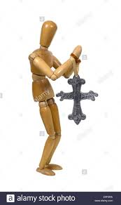 model praying with a large silver cross in his path