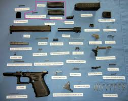 a glock series pistol labeled and broken down into its 34 parts