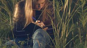 this beautiful young teenage is writing in diary outdoors in