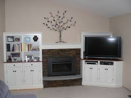 white wooden shelves with doors connected by brown stone fireplace