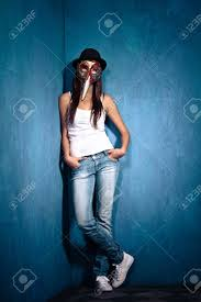 Corner Of Room by Teen Wearing Venetian Mask Black Hat And Blue Jeans Stand