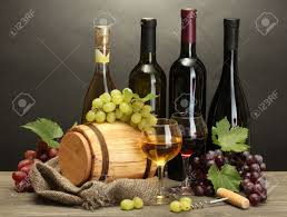barrel bottles and glasses of wine and ripe grapes on wooden