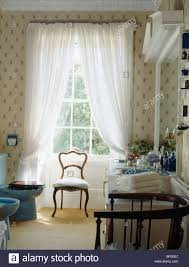 antique chair in front of tall window with white voile curtains in