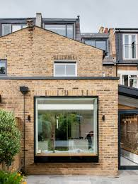 studio 1 architects adds brick extension with large window to