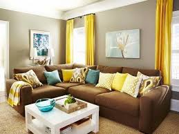 light brown living room greige walls brown couch pops of yellow and aqua roman way