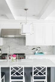 light gray backsplash tiles accent white shaker cabinets flanking