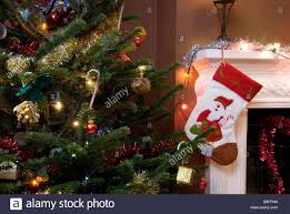 close up on christmas tree and stocking hanging on fireplace stock