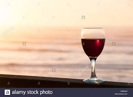 glass of red wine on deck railing of house on the beach at yachats