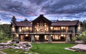exterior home at dusk with lighting and 2 level plus stone pillar