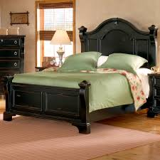 black stained wood queen bed with wood headboard and green bed
