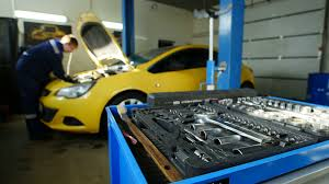 colors close to yellow worker works in professional car workshop near yellow car time