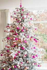 snow sprayed white flocked tree with pink and green balls and