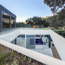 the conversation pit makes a much appreciated comeback at an a bridge of steel grating leads to the garage and the entrance both on the