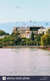 beau rivage palace hotel building with flags in lake geneva stock