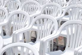 white plastic chairs disposed in rows on the street stock photo