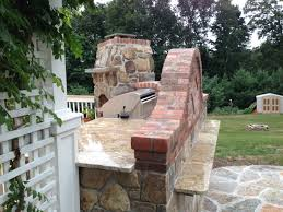 outdoor kitchen designer blends bricks with stone to mesh the brought to the top with the yellow river granite which also pulls the yellow stone from the fireplace although this isn t my largest outdoor kitchen