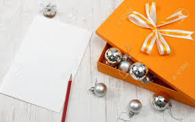 open orange gift box with silver christmas baubles white greeting