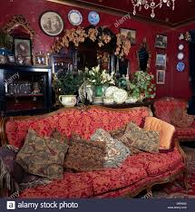 Victorian Style Living Room Red Patterned French Style Sofa Piled With Cushions In Dark Red