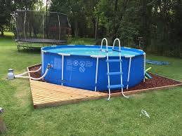 simple round pool of intex pool with a small deck has wooden deck