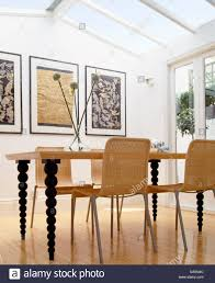 wicker chairs at wooden table with spindle legs in modern dining