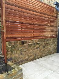 hardwood screen trellis on yellow stock brick wall london house