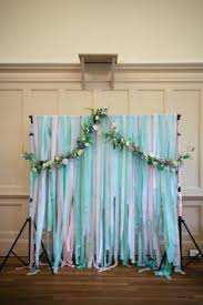 wedding backdrop ideas diy ceremony backdrop using pastel colour streamers and a floral