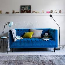 white living room with green and pick leather chesterfield blue