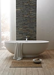 white small freestanding bathtub on wooden floor connected by grey