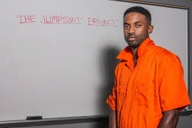 orange jumpsuit wrongfully incarcerated artist finished grad wearing an
