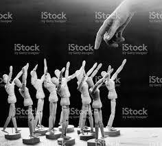 wooden manikins human finger approaches crowd of awestruck wooden manikins