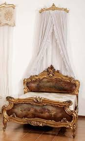 an impressive antique bed in the venetian style in gilt and