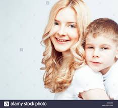 sister curls her brother hair young modern blond curly mother with cute son together happy