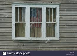 american flag hanging in window of old farm house in michigan usa