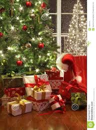 brightly lit christmas tree with lots of gifts stock photo image