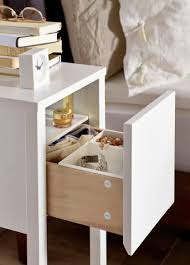close up of small ikea bedside table drawer open to reveal inside