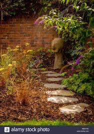 stepping stone path through garden flower bed with bark chippings