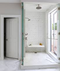 walk in shower with white and gray herringbone tiles and floating