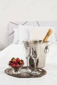 champagne in bed in a hotel room ice bucket glasses and fruits