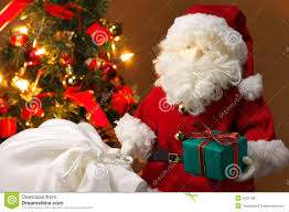 cute stuffed toy santa claus giving a christmas present royalty
