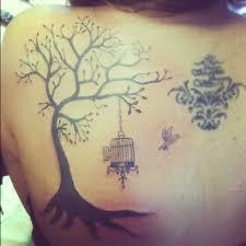 bird cage on tree on back shoulder