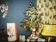 1960s home movie high angle pan toys gifts under christmas tree in
