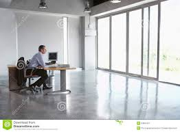 Office View by Man Sitting At Desk In Empty Office Royalty Free Stock Photography