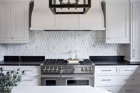 white cabinets with black countertops and backsplash black countertops with white veining transitional kitchen