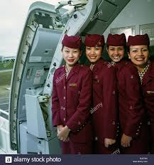 airline cabin crew four cabin crew members wear the uniforms of qatar airways