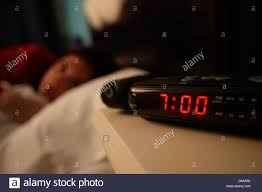 alarm clock early morning with early twenties woman lying in bed stock photo alarm clock early morning with early twenties woman lying in bed in a bedroom