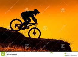Sunset Orange by Silhouette Of Downhill Mountain Bike Rider At Sunset Stock Photo