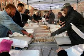 assembly line of volunteers feed turkey dinners to thousands of