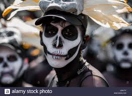 halloween in mexico a mexican man wearing a skull mask and having his face painted